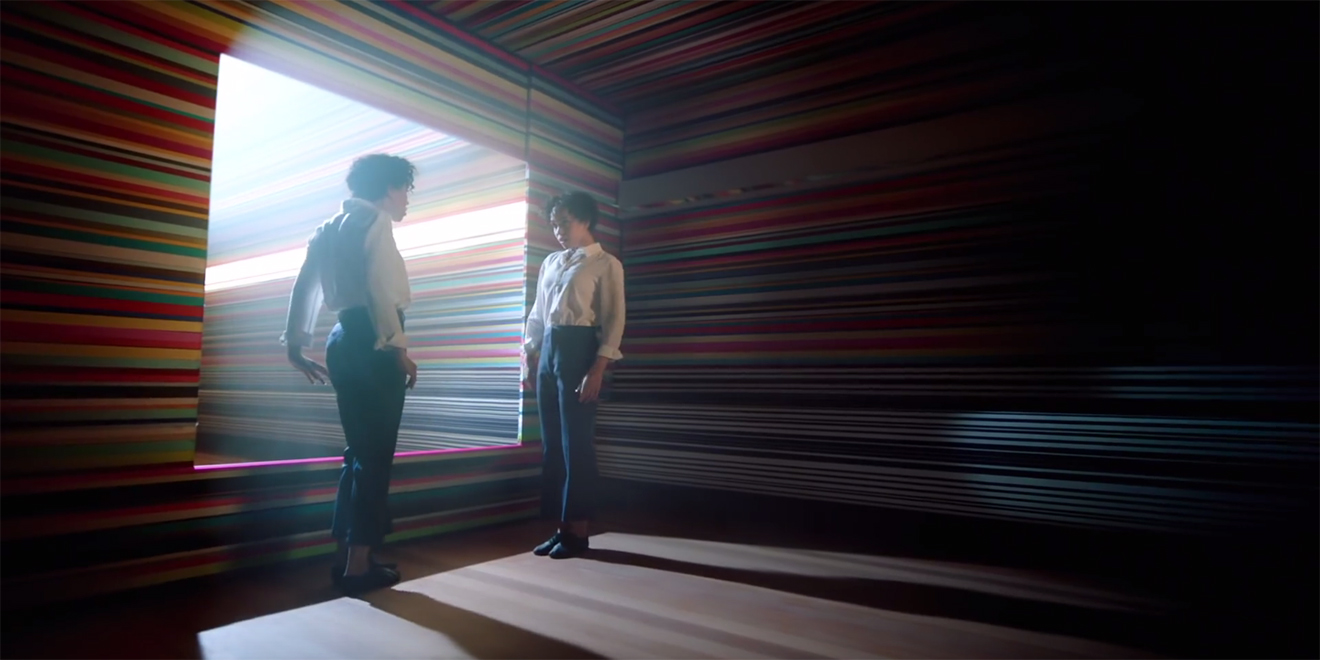 Two people stand face to face; they are in a rainbow colored room with one large window in the middle