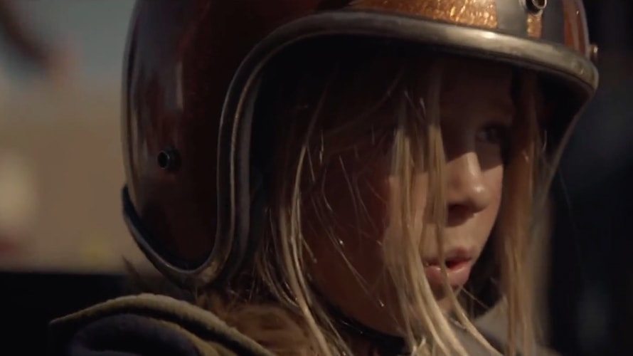 A blonde girl is wearing a helmet as she looks off into the distance; the image is taken from an Audi advertisement