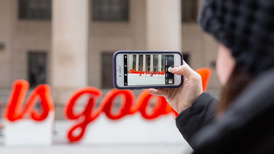 A woman is taking a picture on her phone of the sculpture.