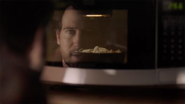 a reflection of a microwave door; the man is making popcorn