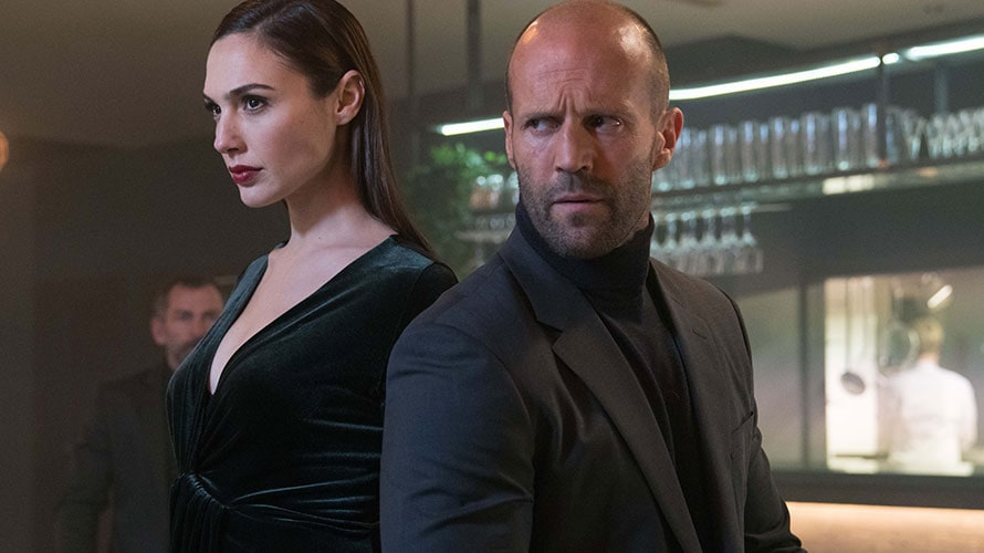 Jason Statham and Gal Gadot standing back to back in a commercial