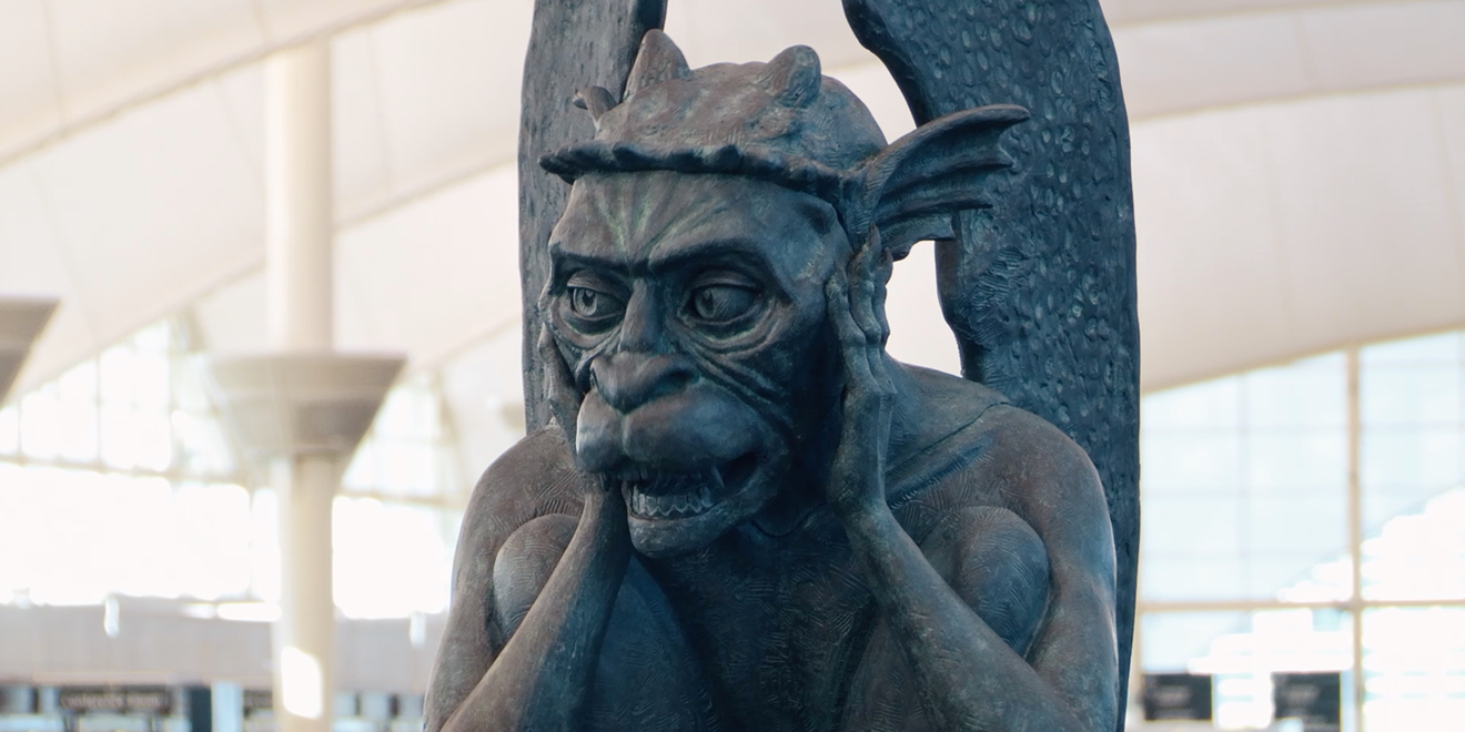 Gargoyle at Denver International Airport has its hands on the sides of its face.