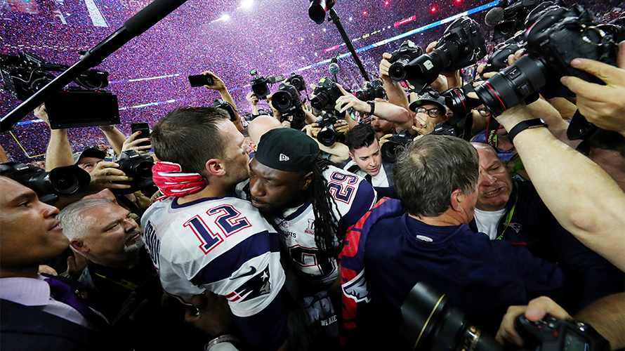 Tom Brady sharing an embrace with his teammate following a Super Bowl championship
