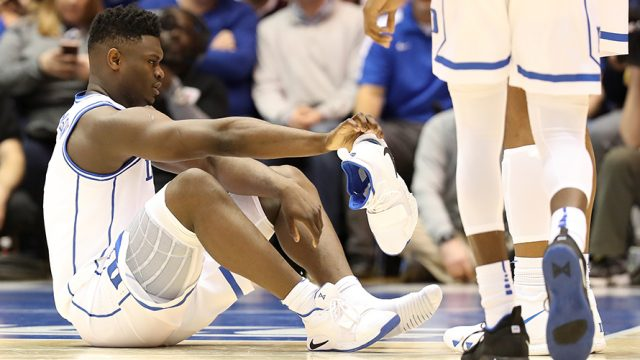 Duke's basketball star, Zion Williamson sits on the floor of the basketball court after his Nike shoe exploded