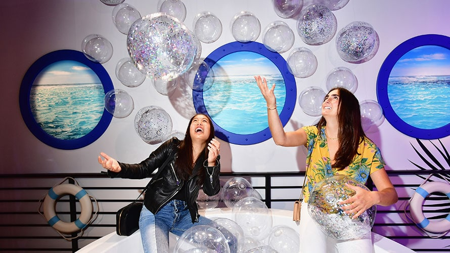 On what appears to be a cruise ship; the two women toss bubbles in the air