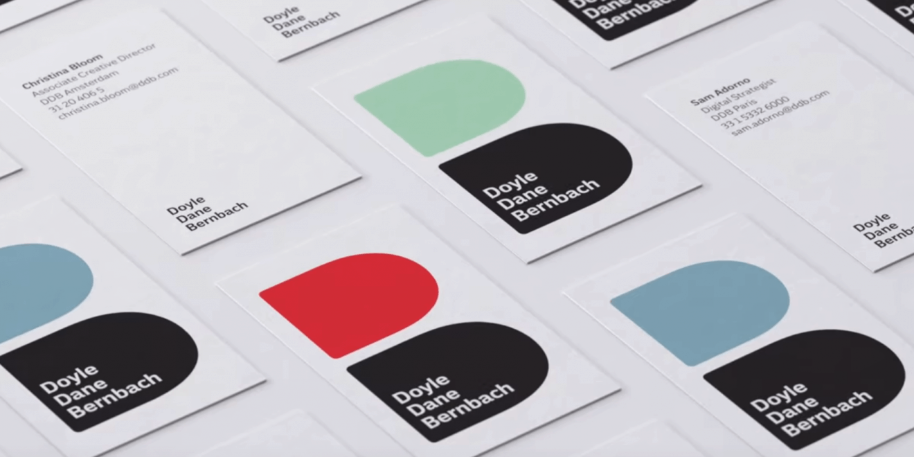 Business cards show D's in solid colors stacked to form B's in DDB's logo.