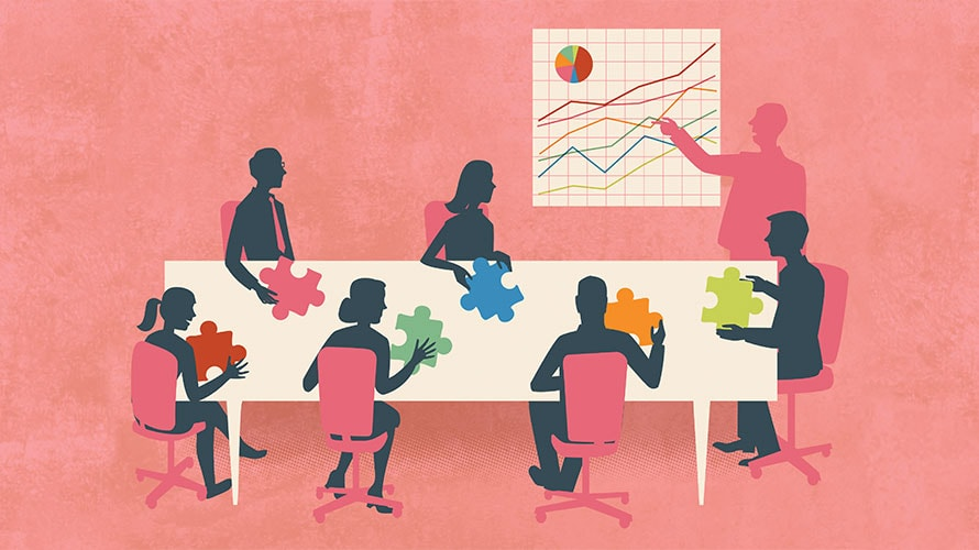 employees sitting around a conference table; each person hold a piece to the puzzle; one person stands and points at a line graph