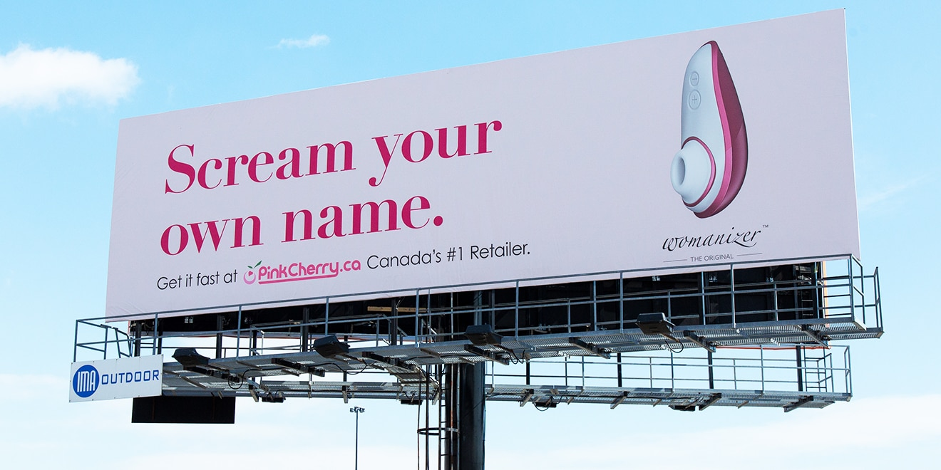A Canadian sex toy ad is displayed on a billboard facing a popular highway.