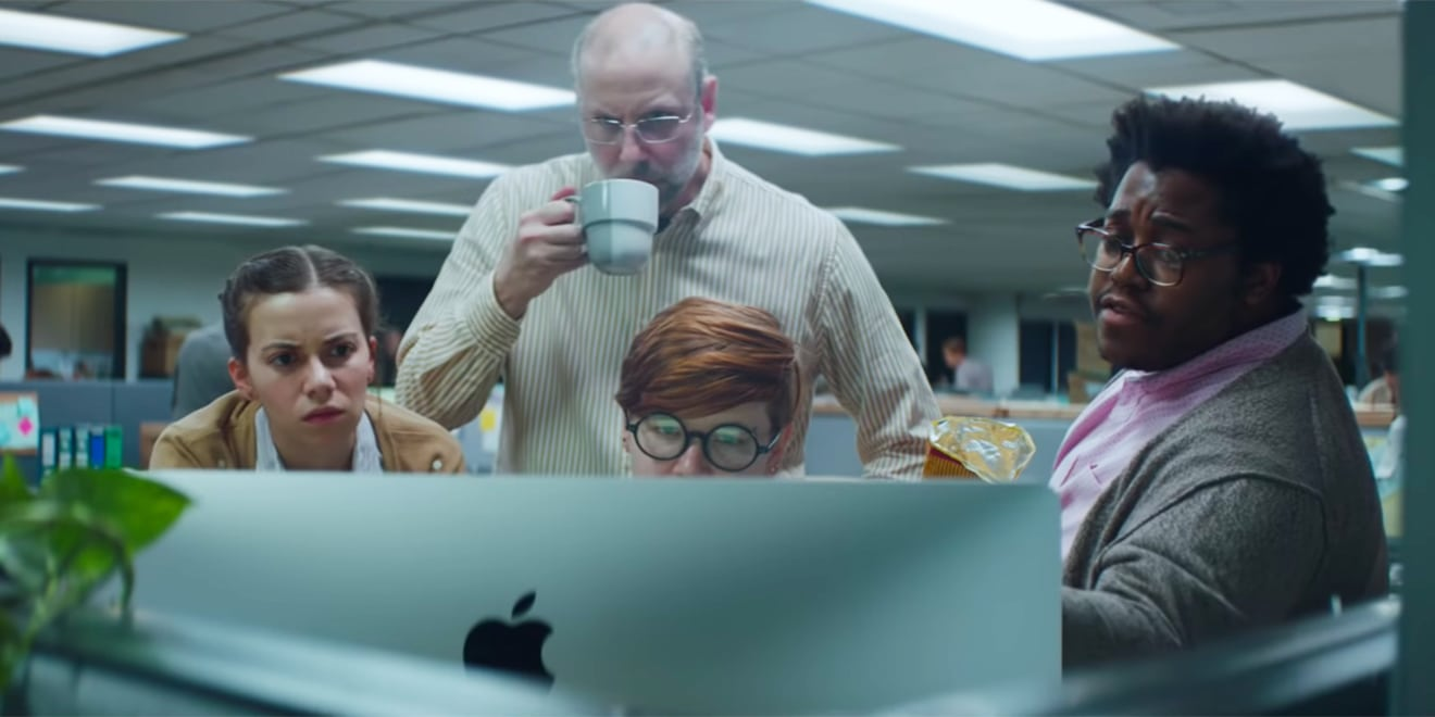 A cluster of co-workers gather around an Apple computer.