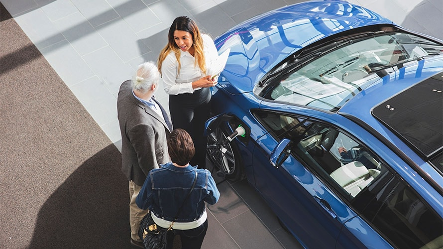 A couple stands next to a car salesmen; The sales lady is trying to sell the couple an electric car