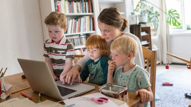 A mom is sitting on a chair using her computer; she is teaching her three children how to use the computer