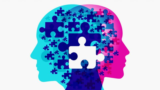 Two heads face away from each other; The left head is blue; The right head is pink; between the heads are puzzle pieces