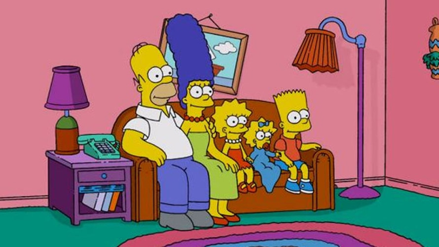 The Simpsons sit on their couch in the living room.
