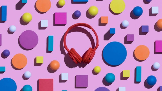 Pink background with colorful shapes and red headphones.