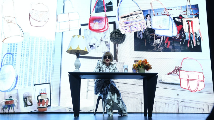 A woman is sitting behind her desk; on her desk are flowers and a lamb; behind the woman is a screen with sketches of bags