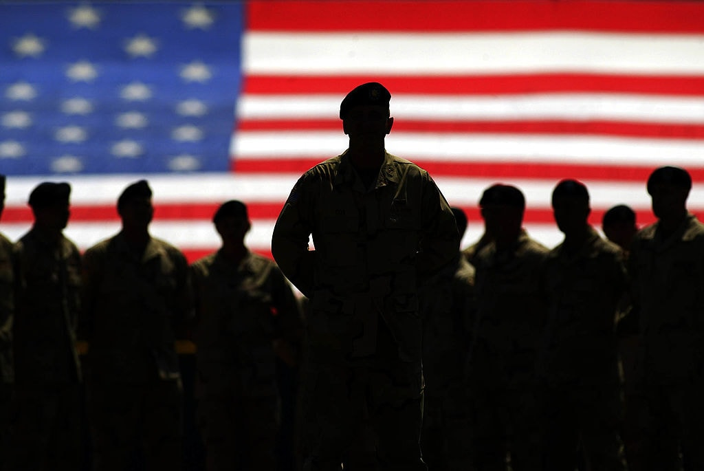 Silhouettes of Army members in front of American flag