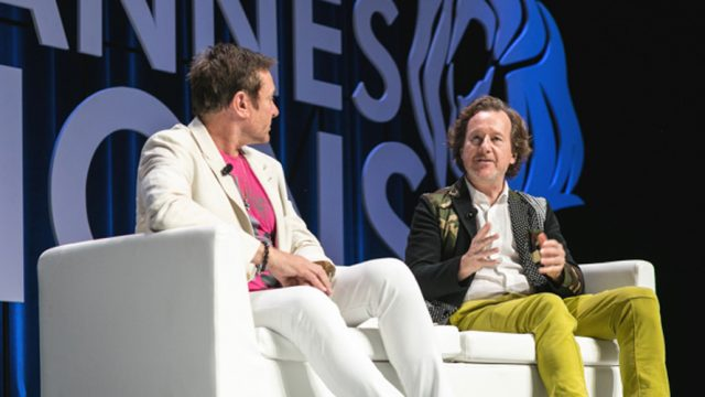 Two men sit on a white couch and have a conversation at a Cannes Lion event