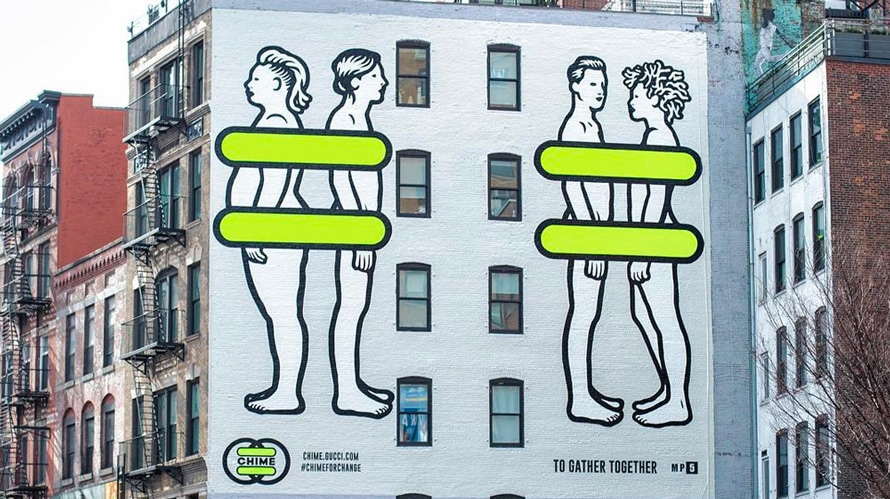 On the side of a building their are four people; two people facing each other and two people facing away from each other; green strips cover their private parts of their body's