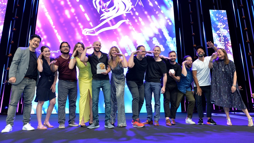 A group of people posing on a stage at Cannes Lions; A man in the middle holds a trophy
