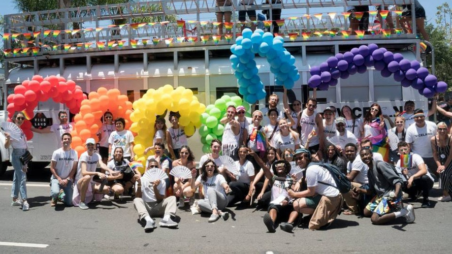 A group of people in front of rainbow colored balloons