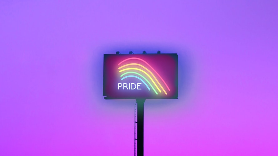 A billboard that says the word 'Pride'; a rainbow on the billboard