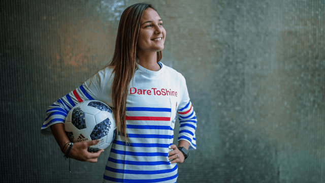 "Female Soccer star poses with a soccer ball in a red, white, and blue striped shirt that says ""Dare to Shine"""