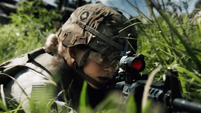 Soldier in dense foliage aiming a gun