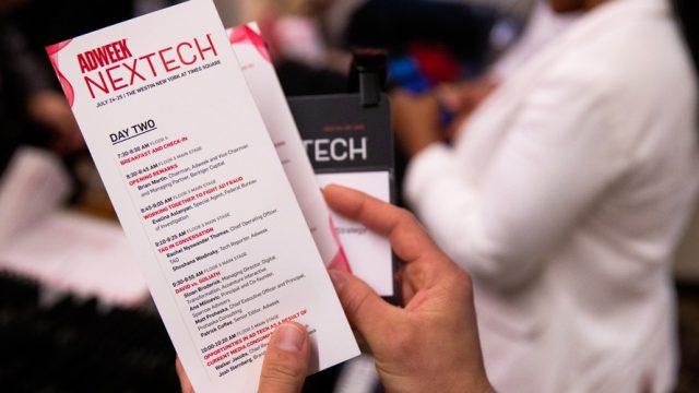 Hands holding an Adweek Nextech brochure
