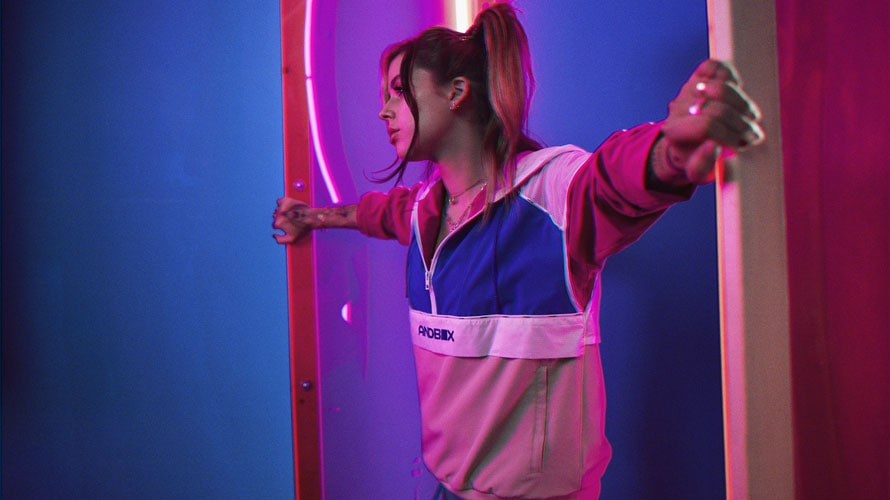 Female model wearing Andbox pullover with arms spread across the room