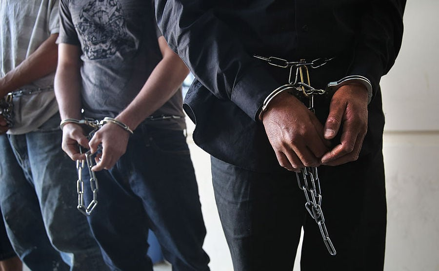 Handcuffed people stand in a prison.