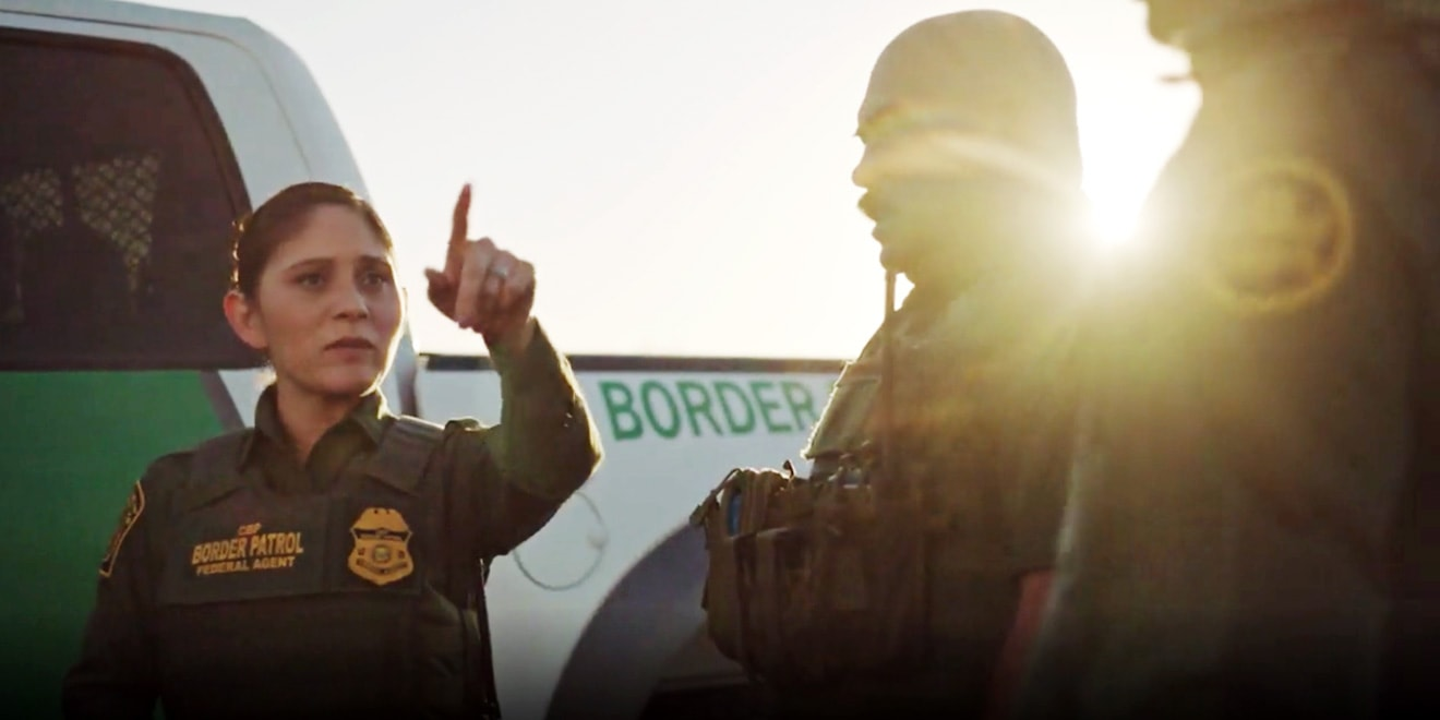Female U.S. Customs and Border Protection agent pointing something out to her colleagues.