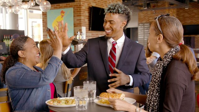 Francisco Lindor high-fiving a woman at a table in a restaurant