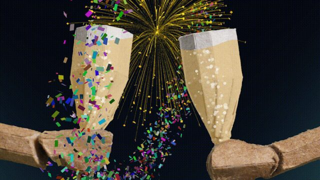 Cardboard illustrations of two people making a toast surrounded by confettis and fireworks