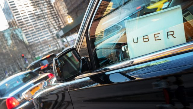 Close up side profile of a car with the Uber logo inside by the window
