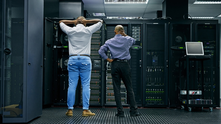 two men looking at computer servers with their backs turned looking frustrated or confused