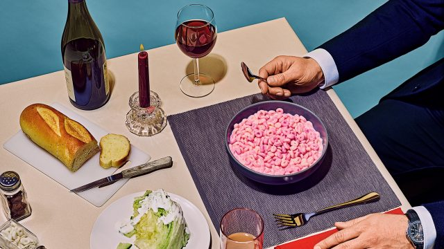 A person eating a pink bowl of cereal with an assortment of other foods on the table like wine and bread.