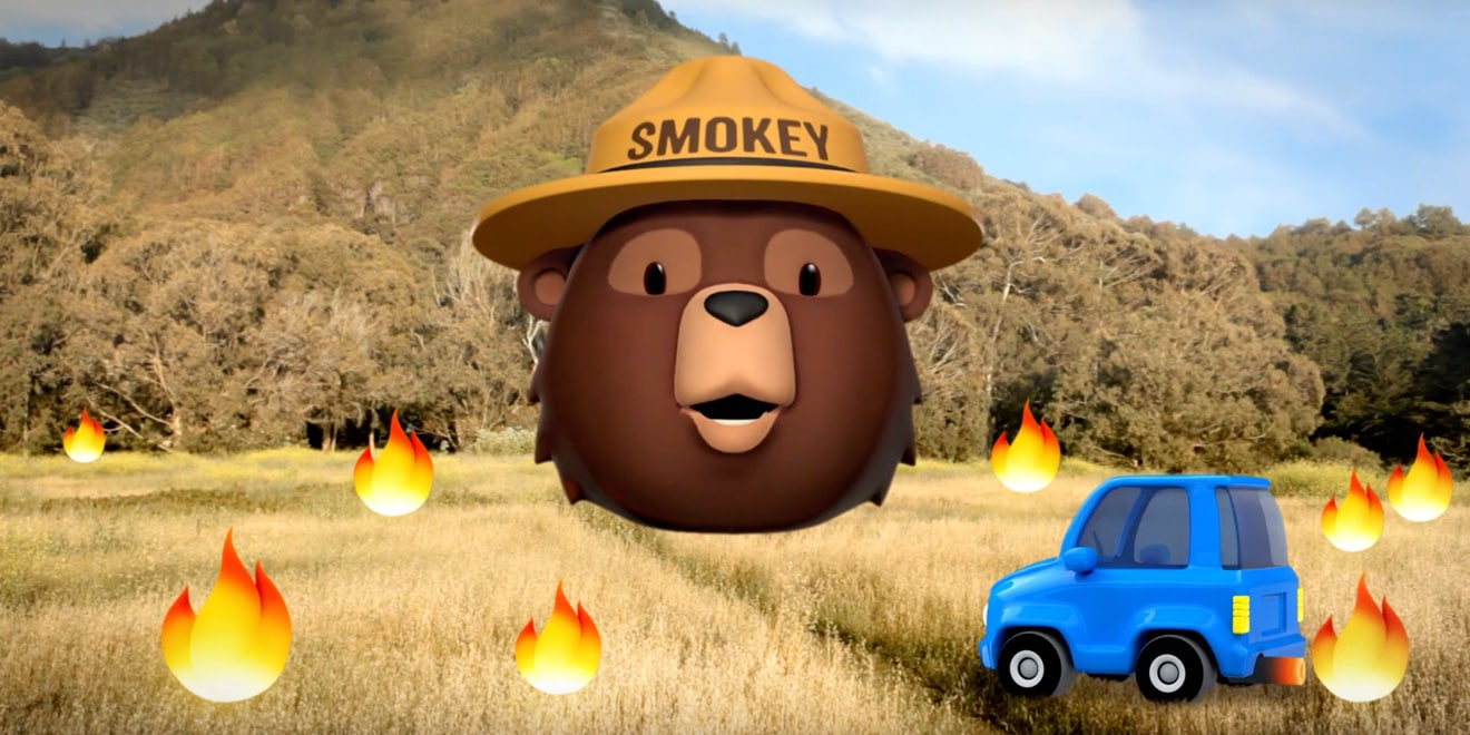 Smokey Bear in forest surrounded by fire emojis and one blue car emoji