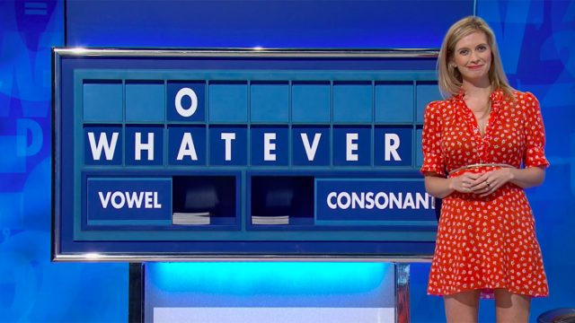 rachel riley in red dress standing next to a sign displaying the word whatever