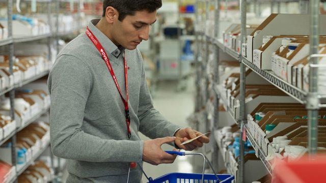 CVS pharmacist with shopping basket consults a list and peruses medications