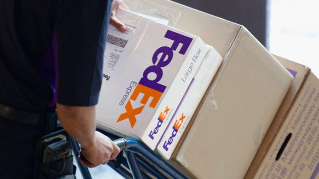 FedEx delivery man pushing packages with a trolley