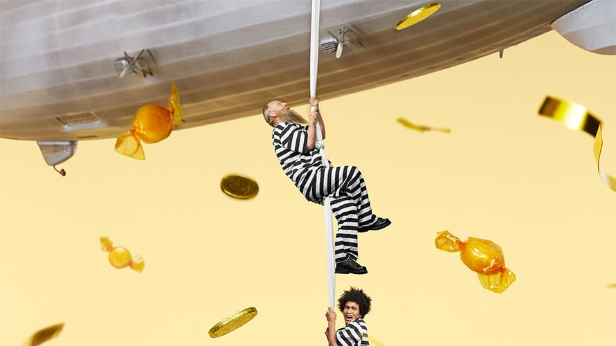 Two people in prison stripes climbing a rope into a blimp.