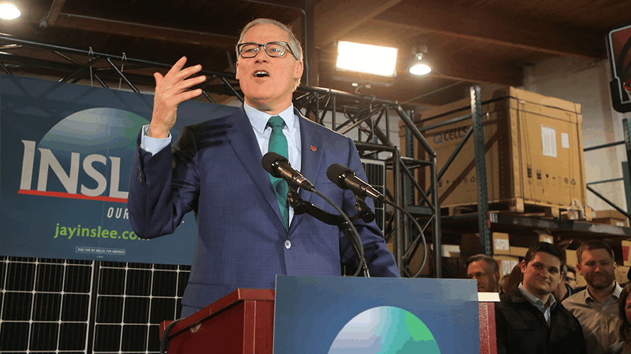 Presidentail candidate Jay Inslee speaks at a podium surrounded by his campaign's branding
