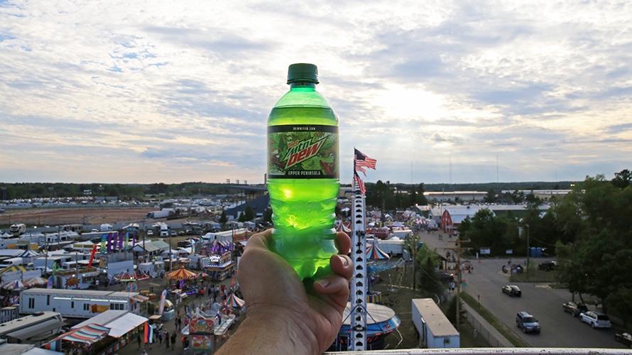 mountain dew bottle held up against a sunset near a fair