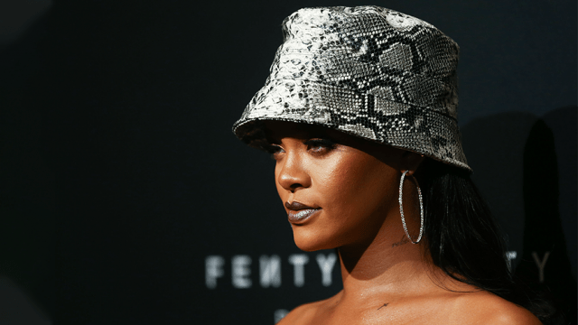 A photo of Rihanna with a silver hat on and FENTY in the background.