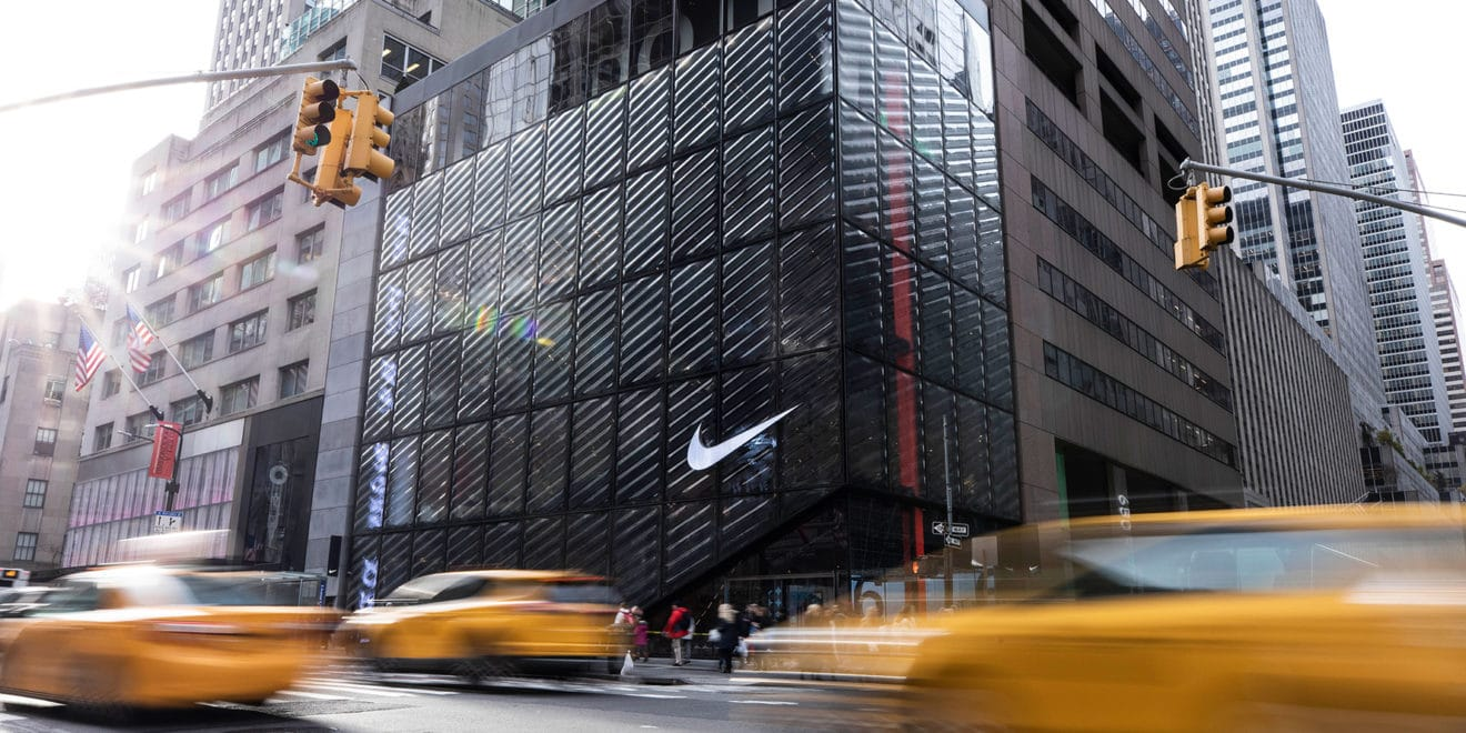blurry cabs driving past a Nike store