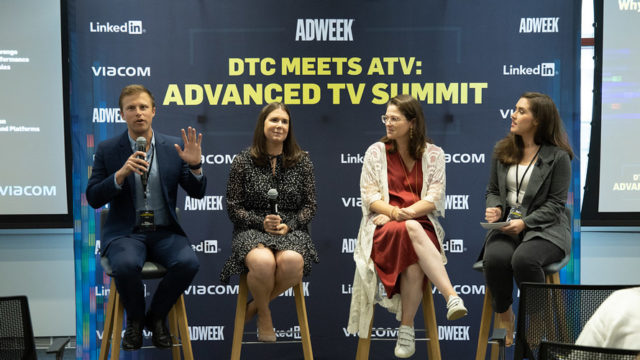 One man and three women talking on a panel.