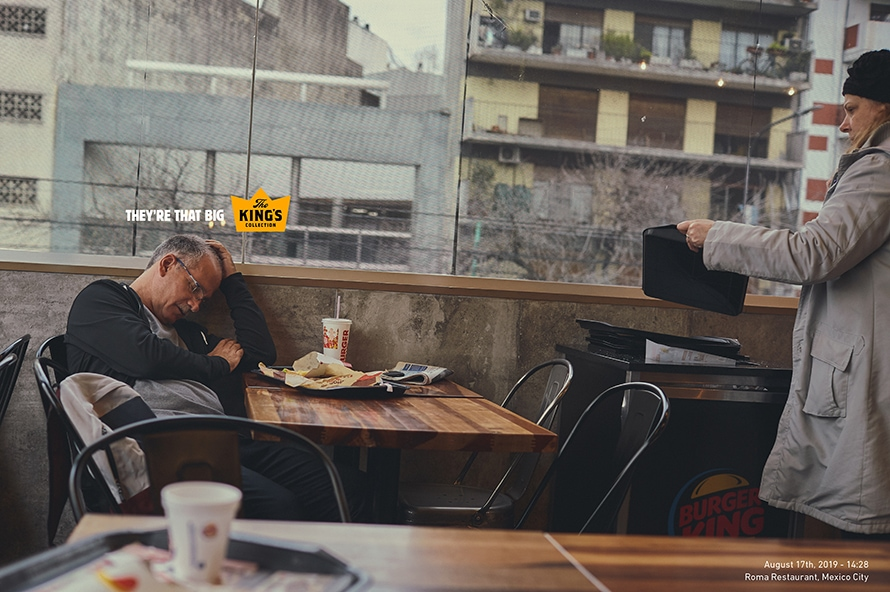 A man leans against the wall as he naps at a Burger King table.