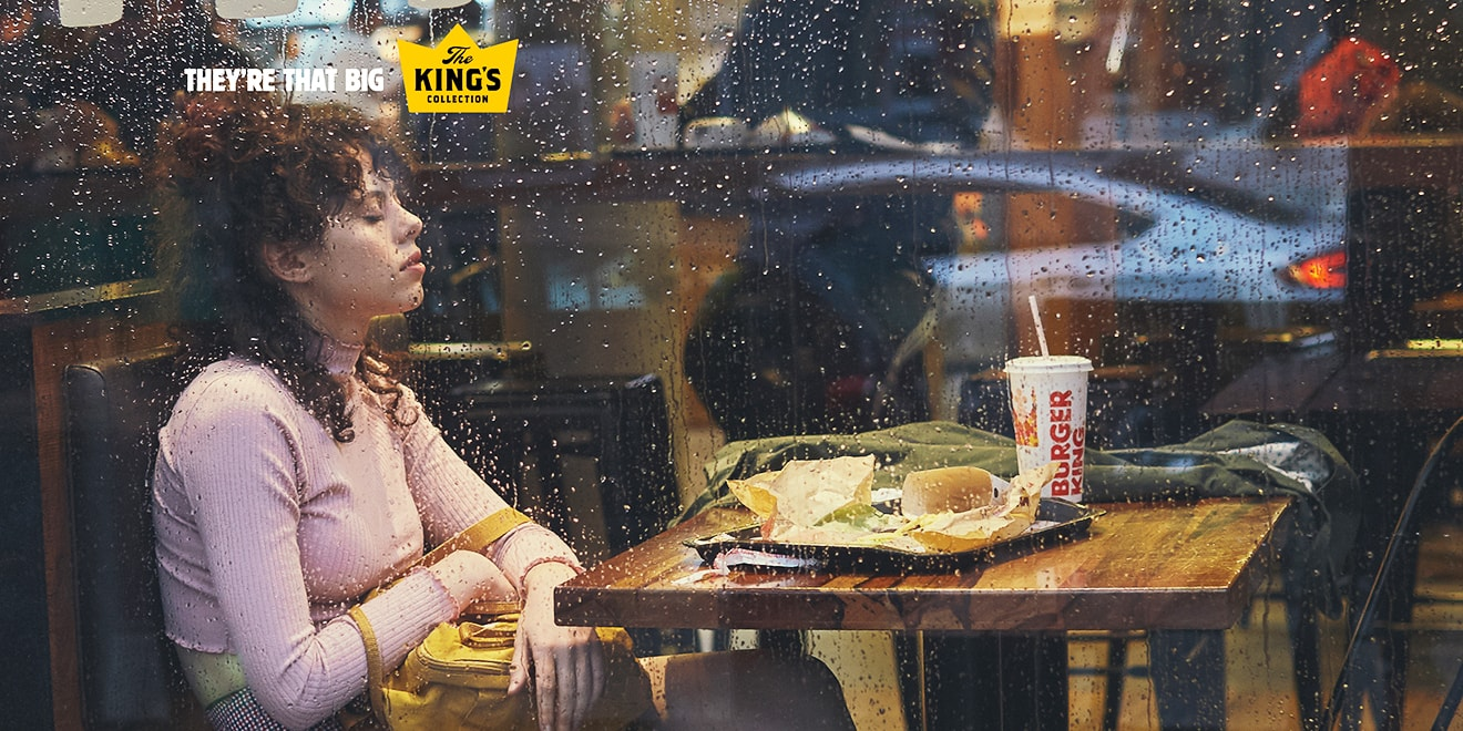Rain splatters a window as a Burger King customer falls asleep sitting in her booth.