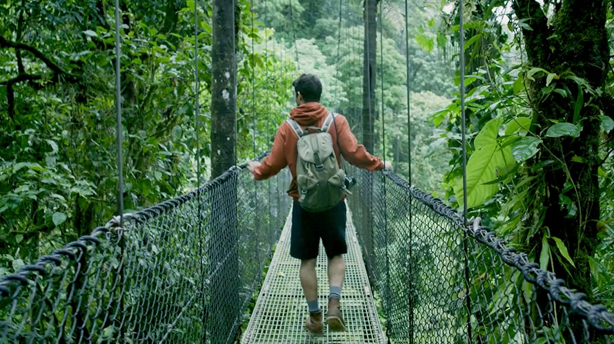 A hiker walks across a bridge in Costa Rica