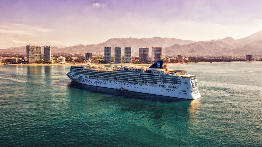 image of a cruise ship with mountains and buildings in the background